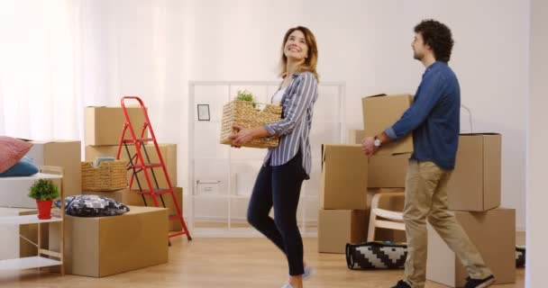 Attractive Caucasian couple coming in the new cozy apartment and bringing carton boxes and home stuff there as moving in it. Indoor