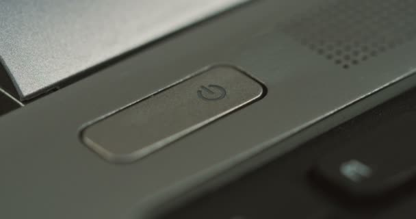 Macro of the female finger pressing the button of turning on the black laptop computer. Close up