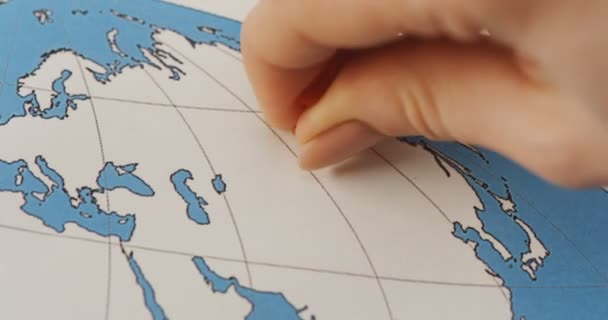 close up of the female hand piercing a map with pins on the place of