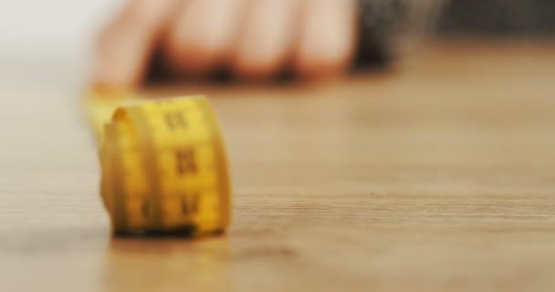 Közelről a sárga méter szalag gördülő a fából készült asztal. Makró
