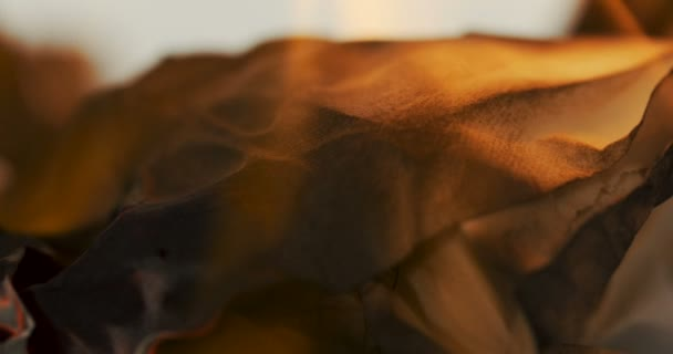 Makro z listu papíru v plamenech před kamerou. Hořící stránka. Detailní záběr