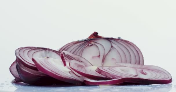Macro of the cutted fresh purple onion rolling in front of the camera with drops of the water on the white background. Close up