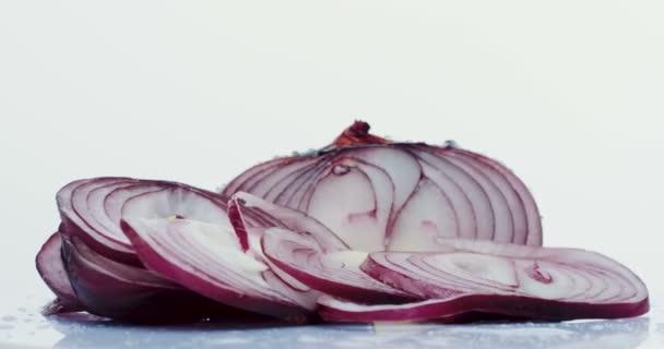 Makro krájená čerstvá fialové cibule válcování před kamerou s kapky vody na bílém pozadí. Detailní záběr
