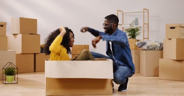 fröhliches afrikanisch-amerikanisches Paar beim Einzug in die neue Wohnung. lockige Frau, die im Karton sitzt und Spaß mit ihrer Freundin hat. Innenräume