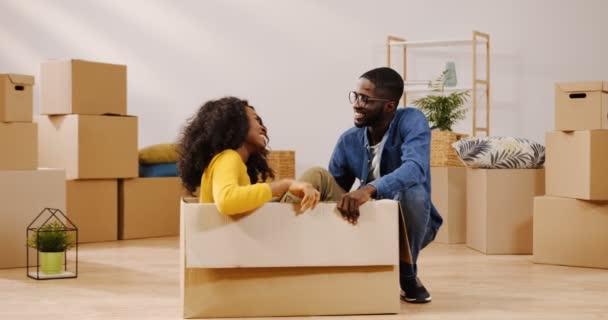junge lockige afrikanisch-amerikanische Frau sitzt in der Kartonschachtel inmitten des gemütlichen Zimmers zwischen Schachteln, redet und lacht mit ihrem Freund. drinnen