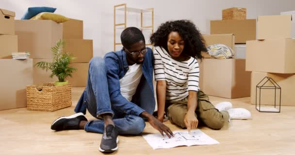 Portrait shot of the married African American young man and woman sitting on the floor among boxes with home stuff and looking at the apartment plan, considering an interior for a new home. Indoor