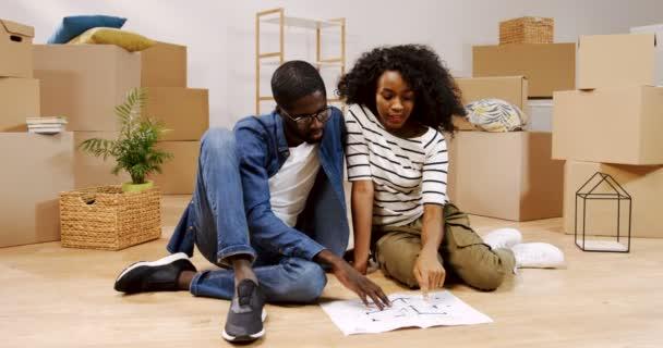Portrét shot ženatý afroamerické mladý muž a žena sedí na podlaze mezi boxy s domácí věci a při pohledu na plánu bytu, vzhledem k tomu, interiér pro nový domov. Vnitřní