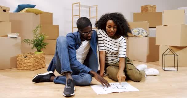 Giovane coppia afroamericana seduta sul pavimento circondato da finestre di fronte il piano appartamento e considerando un interno per la camera. Colpo del ritratto. Al chiuso