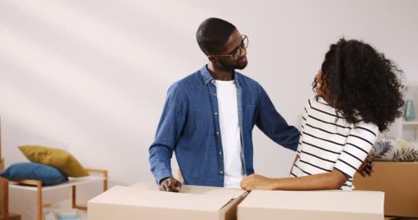 Portrét shot veselá africká americká novomanželům pár stojící poblíž boxy v obývacím pokoji, na sebe dívali, objímání před kamerou a zobrazení klíče od svého nového bytu
