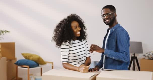 Portrét shot radostné afroamerické jen ženatý muž a žena stojící s lóžemi v místnosti, na sebe dívali, směje se a pak klíče od svého nového bytu. Vnitřní