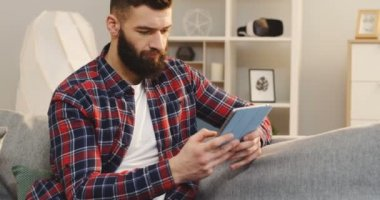 Handsome young man in the plaid shirt and with a beard taping on the tablet device while sitting on the sofa in the cozy living room. Indoors