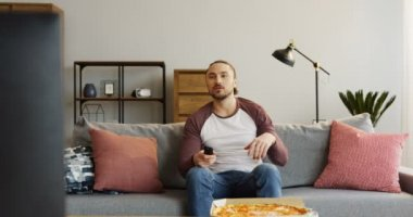 Young attractive man resting in the nice living room, sitting on the sofa and eating pizza. At home. Portrait. Indoor