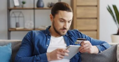 Portrait shot of the young caucasian man holding a tablet device and entering the data of the credit card while buying online. Living room. Indoors