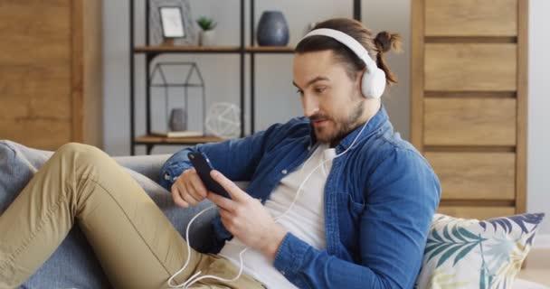 Atraktivní mladý muž ve velké bílé sluchátka a jeans košile pomocí smartphone, usmíval se a díval doma. Vnitřní