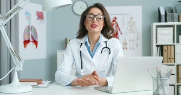 Portrét kavkazské mladé doktorky v brýlích a bílých šatech sedící u stolu s notebookem a mluvící s kamerou jako videozáznam o zdraví. Žena medik bloger mluví o zdravotní péči