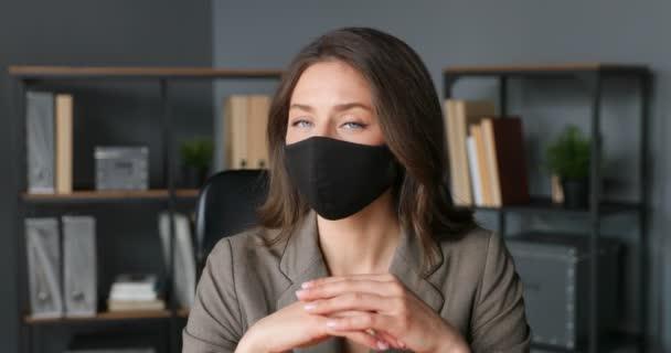 Portrét mladé kavkazské krásné ženy v černé masce sedící v kanceláři a otáčející se tváří k fotoaparátu. Detailní záběr zaměstnankyně nebo šéfky firmy v práci. Koronavirová pandemie. Podnikatelský vzhled.