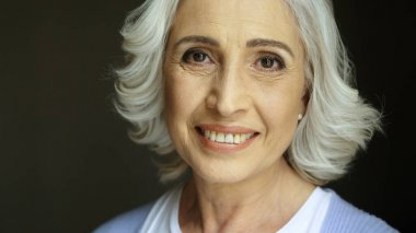 Close up portrait of beatiful old woman with grey hair smiling at camera. Indoor shot. Portrait shot. stock vector