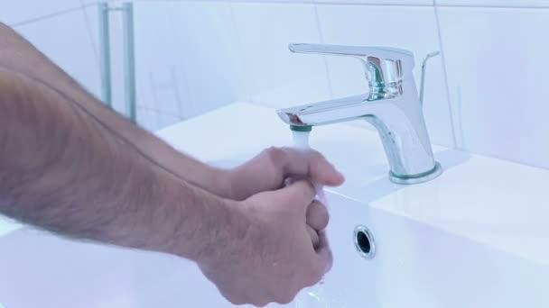az ember mossa a kezét, a víz a fürdőszobában