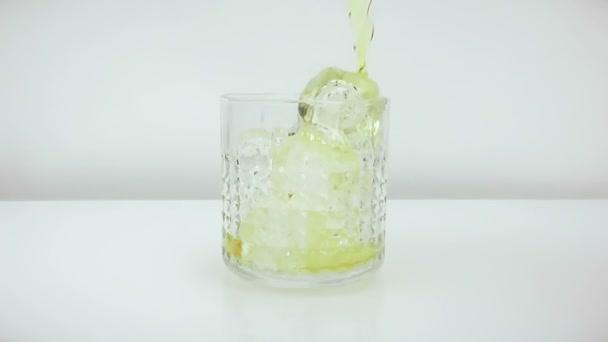 Csapos szakadó whiskyt a jeget, fehér háttér, lassú lövés, az üveg whisky relax