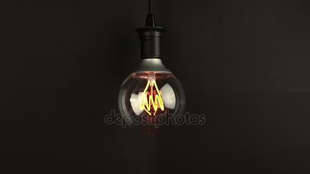 Ein- und Ausschalten, mit Blinkeffekt, Retro-Vintage-Glühbirne mit eingebauter LED-Technologie auf warmem hellgelbem Farbton und schwarzem Hintergrund, energiesparend mit altmodischer Atmosphäre
