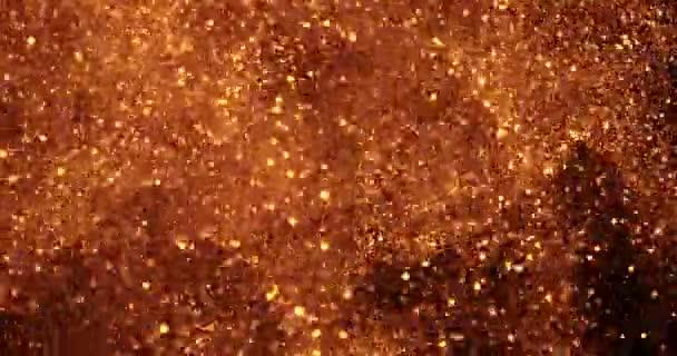 Vánoční zlaté třpytivé glitter výbuchu prachu částice pozadí s konceptem bokeh, zlatý šťastný nový rok dovolená