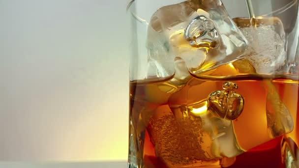 detail z barman nalil whisky v pití sklenice s kostkami ledu na teplém bílém pozadí, čas relaxační nápoj s whisky