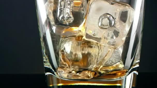 közeli a jeget a fekete háttér, a pohár whiskey szakadó csapos relaxációs ital a whisky idő