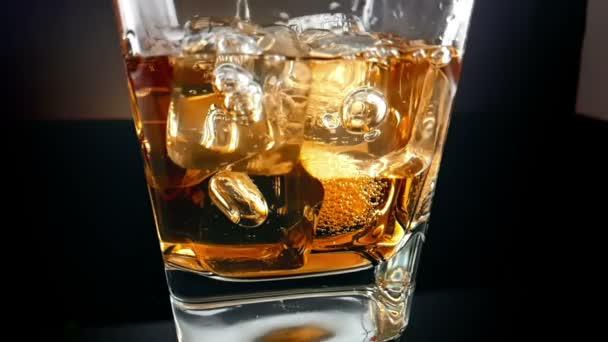 közeli a jeget a fekete háttér, a pohár whiskey szakadó csapos relaxációs ital a whisky, a lassú idő