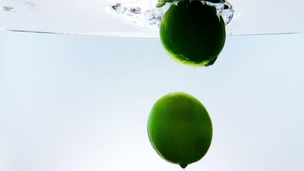 Limetten-Spritzer fällt in weißes Cocktail- und Wassertrinkglas, aufgenommen in Zeitlupe auf weißem Hintergrund, Spaß, Ernährung und Trinken