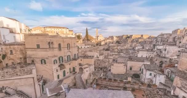 panoramatický pohled na typické kamenů Sassi di Matera a kostel Matera pod modrou oblohou. Basilicata, Itálie s hnutím mraky na obloze