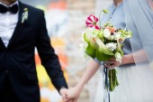 Fotografie cropped view of bride and groom holding hands and bouquet of flowers