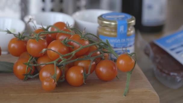 Red cherry rajčátky na dřevěné desce na kuchyňském stole