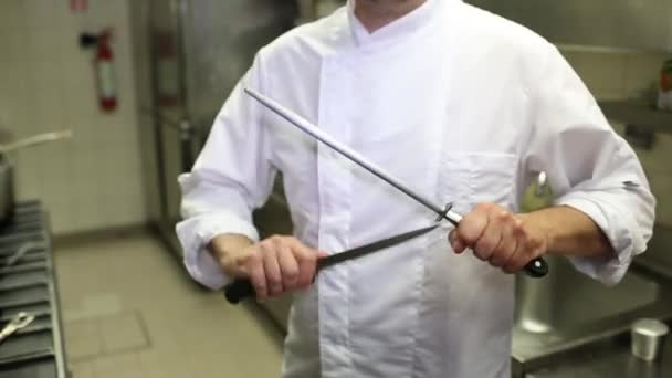 unrecognizable male chief-cooker in white tunic sharpening knife in kitchen of restaurant