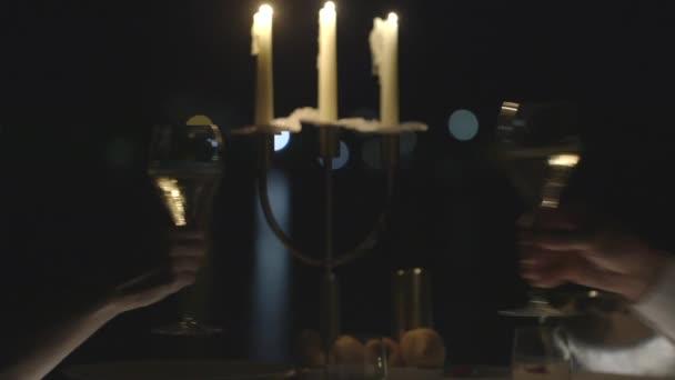 romantisches Candle-Light Dinner, Frau und Mann jubelt mit Gläsern Champagner