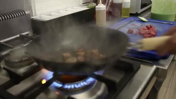 zblízka šéfkuchaře smažení maso v pánvi
