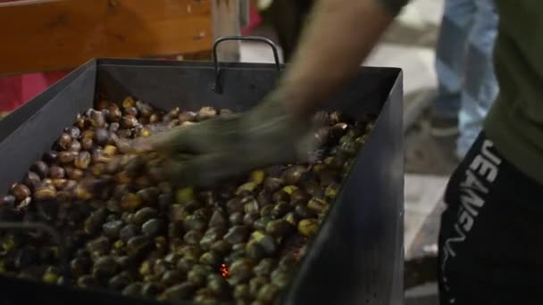 Cropped image of male hand stirring roasted chestnuts in charcoal grill
