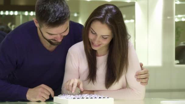 Mladý pár se rozhodne zásnubní prsteny v obchodě šperky