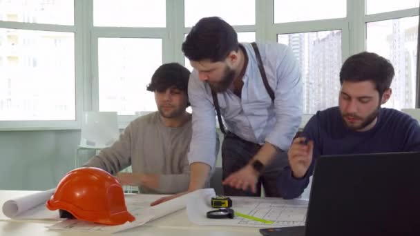 Architekt, ukazující jeho spolupracovník něco o plánech