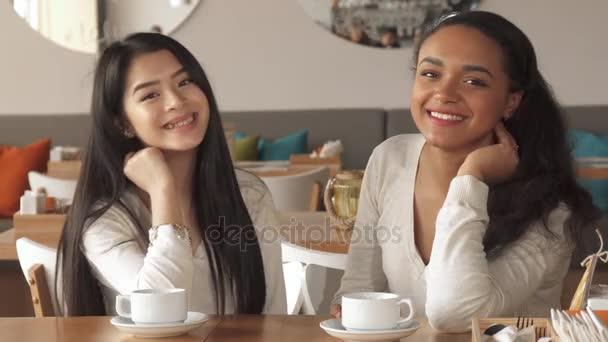 Dvě dívky objetí v kavárně
