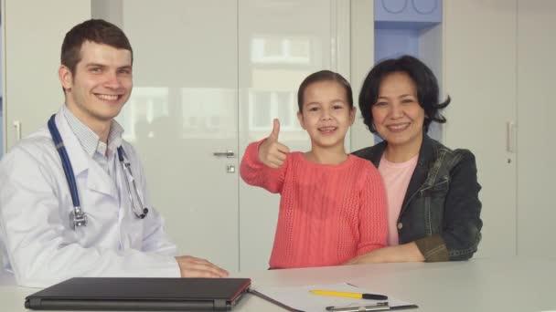 Malá holka ukazuje palec poblíž lékař