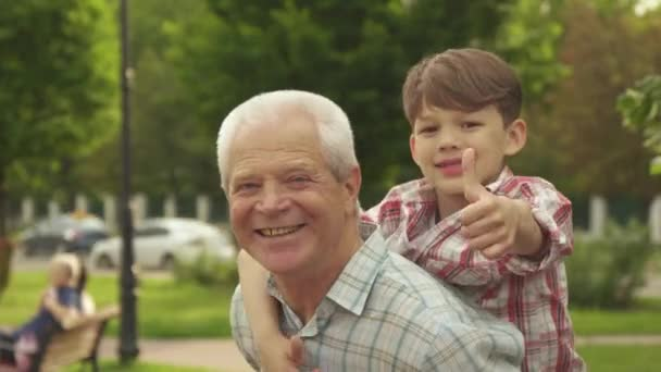 Little boy shows his thumbs up on his grandpas back