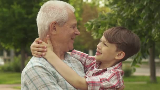 Little boy holds his hands behind his grandpas neck