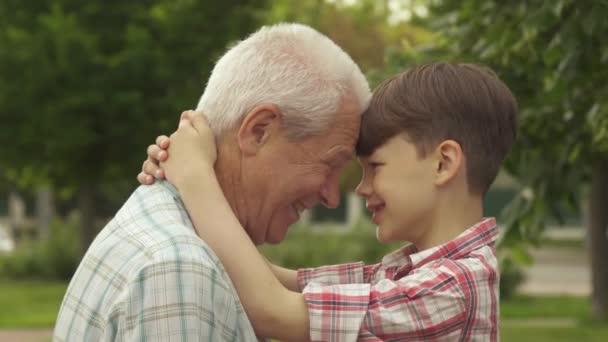 Senior und sein Enkel lehnen die Stirn aneinander