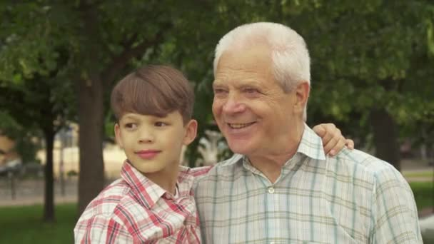 Little boy whispers in his grandpas ear