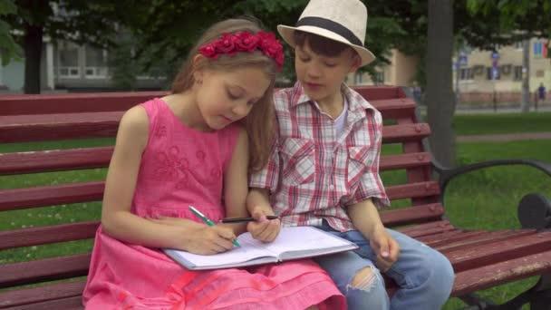 Malá holčička kreslí na jedné stránce poznámkového bloku a její přítel na jiném
