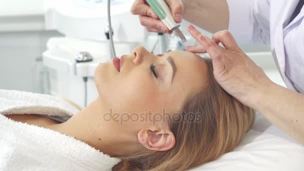 Žena klient získá ultrazvukové peelling pro její tvář