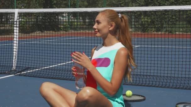 Tenis holka drinring vody při odpočinku na kurtu