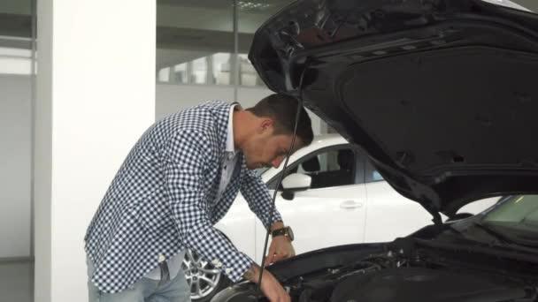 Nový majitel vozu studuje podrobnosti v otevřené hood
