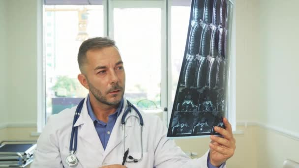 A thoughtful doctor carefully examines an X-Ray shot
