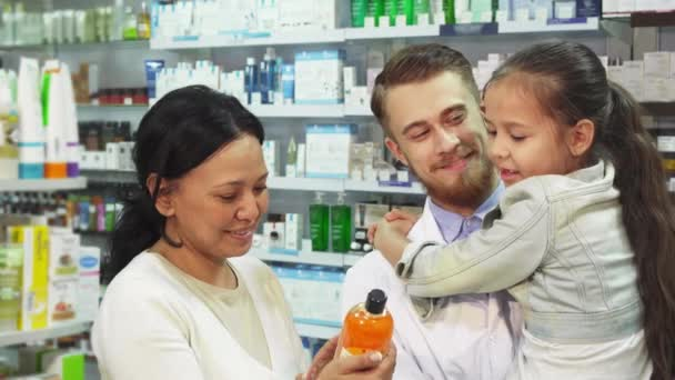 Apothecary with a girl in her arms and her mother choose a remedy in a pharmacy
